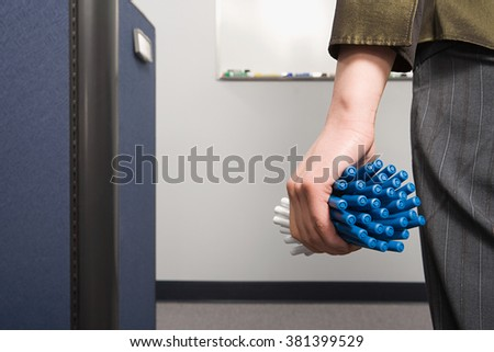 Office worker holding lots of pens - stock photo