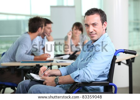 Office worker in a wheelchair with colleagues in the background - stock photo