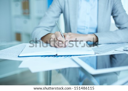 Office worker making notes in her notebook