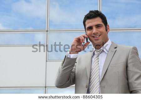 Office worker on phone outdoors - stock photo