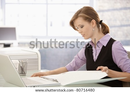 Office worker sitting at desk, doing paperwork.? - stock photo