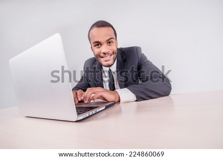 Office worker. Smiling African businessman sitting at a desk on a laptop while a businessman sitting at a desk and is actively working on a laptop isolated on a gray background