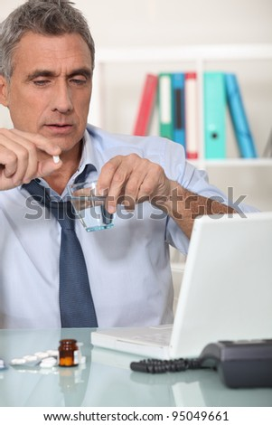 Office worker suffering from hangover - stock photo