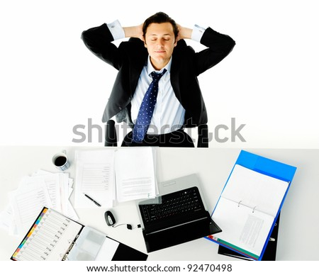 Office worker takes a break from his work and leans back daydreaming - stock photo