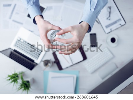 Office worker taking a pill and holding a glass of water hands close up with desktop on background, top view - stock photo