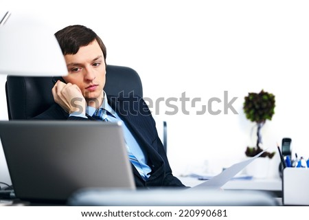 Office worker talking on cell phone in office looking at laptop