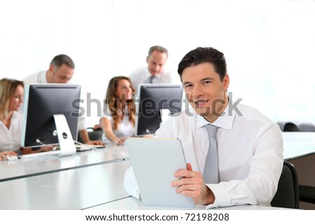 Office worker using electronic tablet in office - stock photo