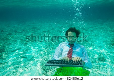 Office worker wearing tie and white shirt with keyboard underwater - stock photo
