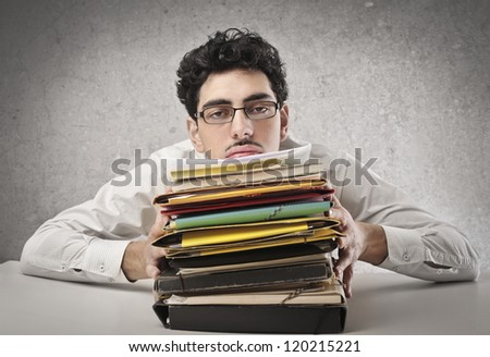 Office worker with a lot of work to do - stock photo