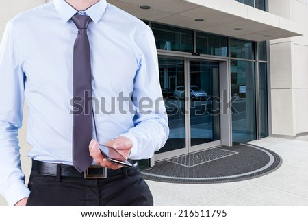 Office worker with cell phone outside the building