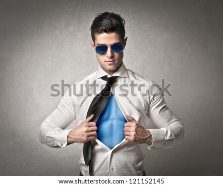Office worker with sunglasses opening his shirt like a superhero - stock photo