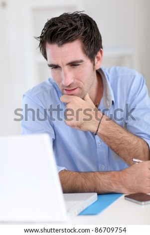 Office worker with thoughtful look in front of laptop - stock photo