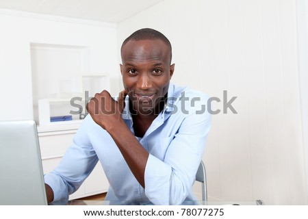 Office worker working on laptop computer - stock photo