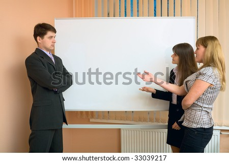 Office workers discuss work standing at a board