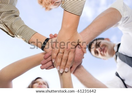 Office workers hold hands together across the sky - stock photo