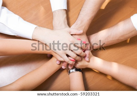 Office workers hold hands together on table - stock photo