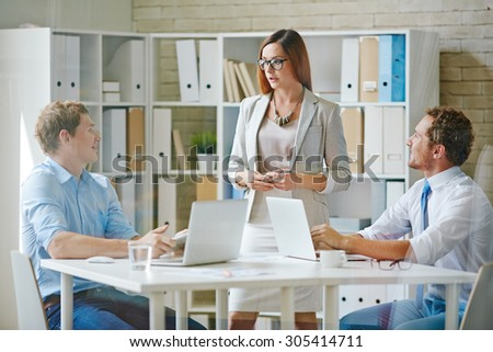 Office workers in formalwear interacting at meeting