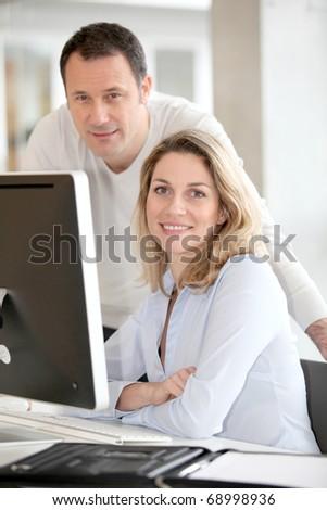 Office workers in front of desktop computer - stock photo