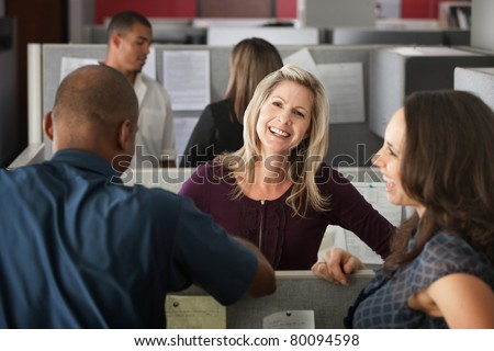 Office workers laugh at a joke shared by colleague