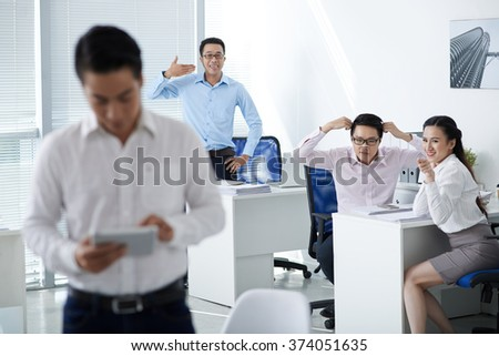 Office workers making mock of their colleague
