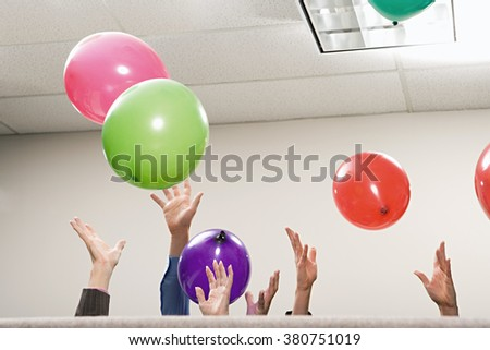 Office workers playing with balloons - stock photo
