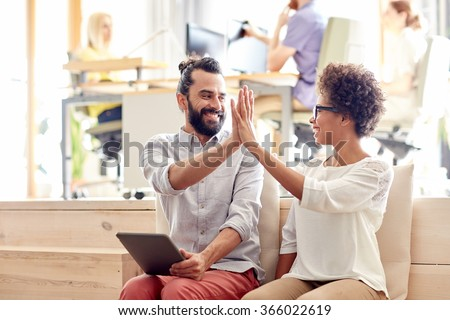 office workers with tablet pc making high five - stock photo