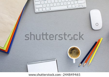 Office working place at morning.  Top view on grey wooden working place with colorful booklets, pens, envelope, computer keyboard, mouse, cup of fresh coffee and blank notepad. - stock photo