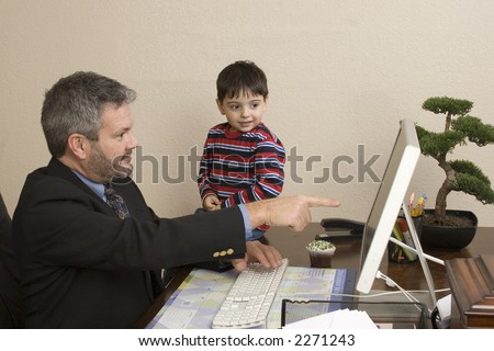 Office working talking to small child sitting on desk.