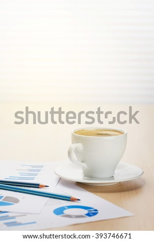 Office workplace with coffee cup and charts on wooden desk table in front of window with blinds with sunset light - stock photo