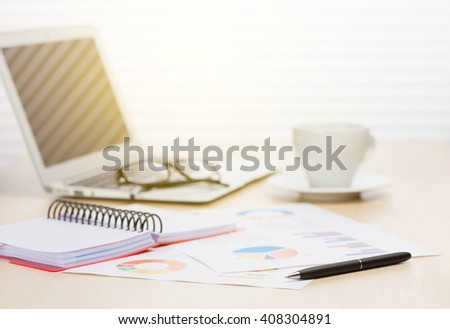 Office workplace with coffee cup, laptop and supplies on wood desk table in front of window with blinds - stock photo