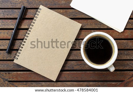 office workplace with keyboard notepad mouse coffee of cup on wooden table. over light