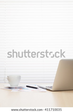 Office workplace with laptop and coffee cup on wooden desk table in front of window with blinds. Business PC over office desk table with copy space - stock photo