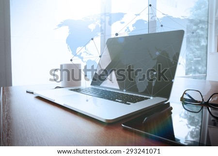 Office workplace with laptop and smart phone on wood table with eyeglasses on digital tablet with social media diagram - stock photo