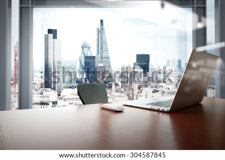 Office workplace with laptop and smart phone on wood table with london city background  - stock photo