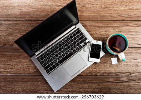 Office workplace with open laptop on wooden desk  - stock photo