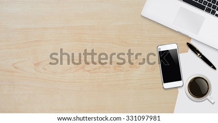 Office workplace with text space ,Wooden table with office supplies smartphone,laptop and coffee cup, top view - stock photo