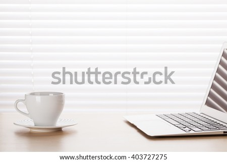 Office workplace with with laptop and coffee cup on wooden desk table in front of window with blinds. View with copy space - stock photo