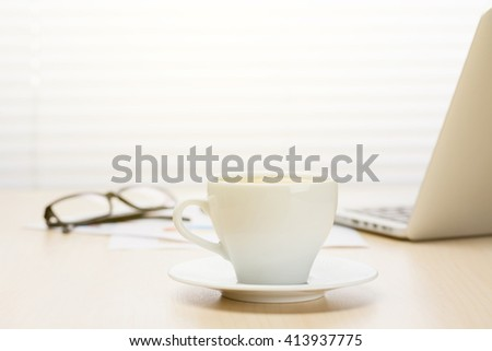 Office workplace with with laptop and coffee cup on wooden desk table in front of window with blinds. Sunset light - stock photo