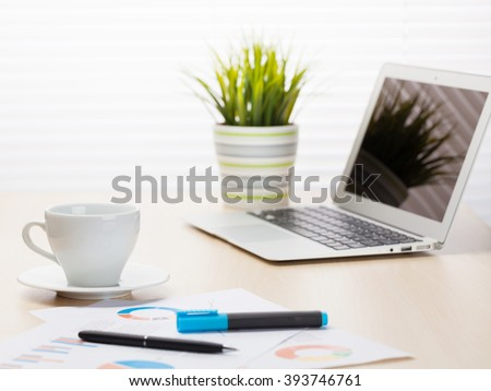 Office workplace with with laptop and coffee on wooden desk table in front of window with blinds - stock photo