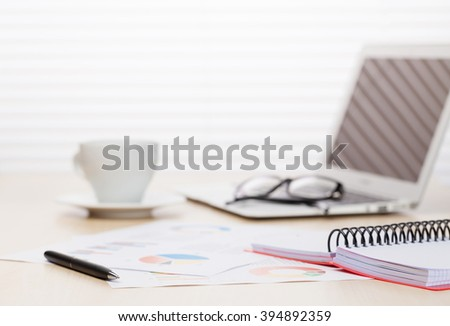 Office workplace with with laptop and coffee on wooden desk table in front of window with blinds. Focus on pen - stock photo