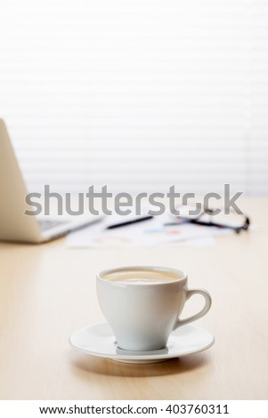 Office workplace with with laptop and coffee on wooden desk table in front of window with blinds. Focus on cup