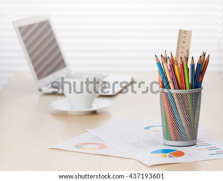 Office workplace with with laptop, coffee cup and colorful pencils on wooden desk table in front of window with blinds - stock photo