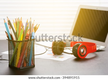 Office workplace with with laptop, reports, headphones and pencils on wooden desk table in front of window with blinds. Sunset light - stock photo