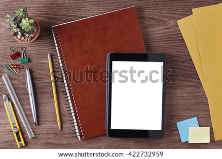 Office Workspace. Top View of a Business Workplace. Wooden Desk Table, Paper Cutter, Ruler, Pen, Pencil, a Blank Screen Tablet, Notebook, Envelope, Plant Pot, Clips. Copy space for text or Image - stock photo