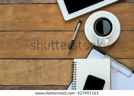 Office workspace with blank screen tablet, cup of coffee, pen, notebook, smartphone and paper over blackboard. Top view with copy space - stock photo