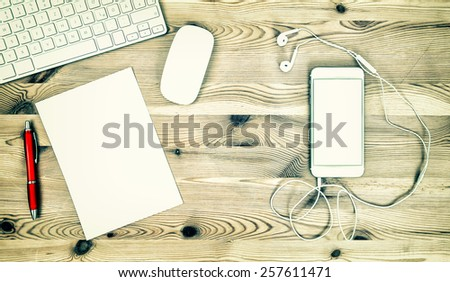 Office Workstation with Keyboard, Phone, Headphones, Paper and Pen. Retro style toned mock up  - stock photo
