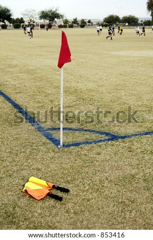 Official's hand flags resting at the corner of a soccer field. - stock photo