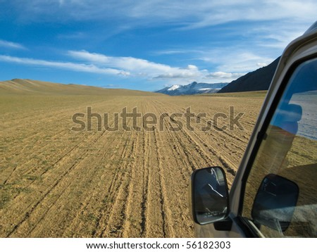 Offroad: car driving on a sand path in Ladakh, India Shot on the way to the Tso Moriri Lake. - stock photo