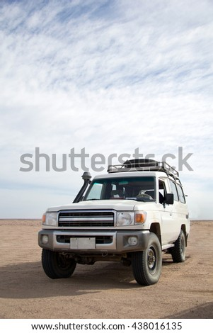 Offroad jeep safari vehicle parked in the middle of the desert - stock photo
