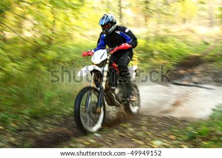Offroad motorbike crossing river, water splashing. Motion blur. - stock photo